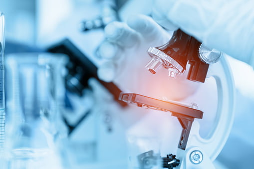 Scientist using microscope in laboratory room while making medical testing and research