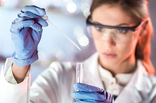 Female life researching in laboratory. Focused on pipetting solution into the glass cuvette